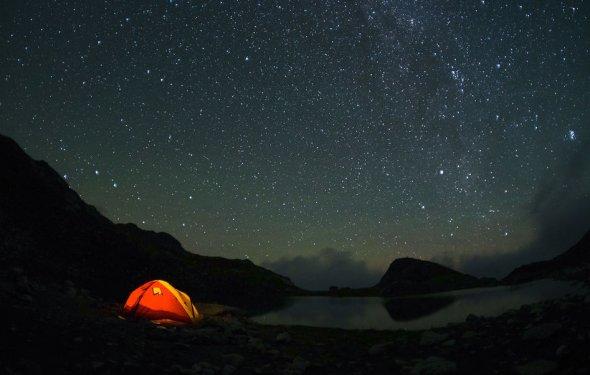 Обои Красная туристическая палатка, стоящая в горах возле деревьев
